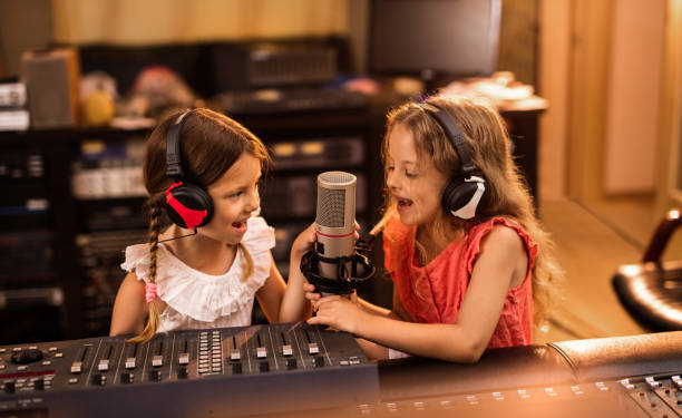 Two small girls having fun in a radio station while talking on a microphone.